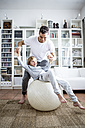 Father and son with fitness ball at home - WESTF22999