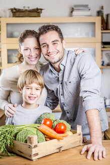 Smiling family with box of vegetables in kitchen - WESTF23005