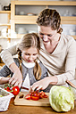Mother and daughter cutting tomatoes in kitchen - WESTF23014