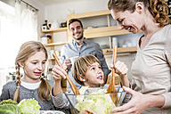 Family preparing salad in kitchen - WESTF23017