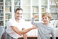 Boy flexing muscles for father at home - WESTF23026