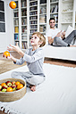 Boy juggling with oranges at home - WESTF23035