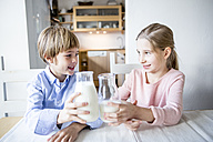 Brother and sister clinking milk glasses - WESTF23047