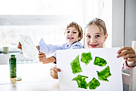 Girl holding paper with painted recycling symbol - WESTF23050
