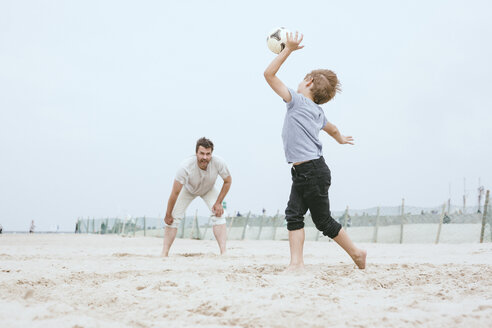 Father and little son playing with ball on the beach - MVCF00154