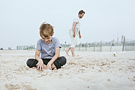Smiling little boy sitting on the sand on the beach while his father playing with ball in the background - MVCF00157
