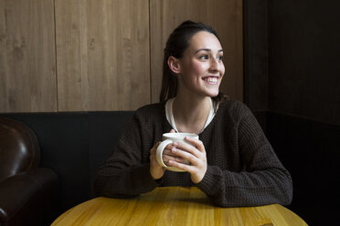 Portrait of smiling woman with cup of coffee in a coffee shop - ABZF01969