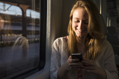 Smiling young woman on a train looking at cell phone - ABZF01978