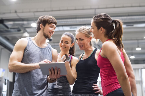 Group of happy athletes with tablet after exercising in gym - HAPF01616