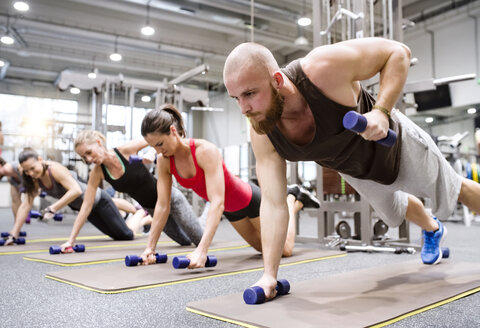 Group of athletes exercising with dumbbells in gym - HAPF01619