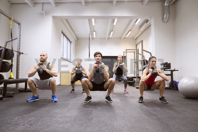 Group of athletes exercising with kettlebells in gym - HAPF01631 - HalfPoint/Westend61