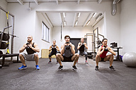 Group of athletes exercising with kettlebells in gym - HAPF01631