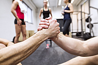 Athletes shaking hands in gym - HAPF01640