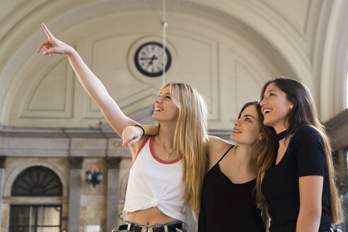 Three young women watching something at concourse - KKAF00725