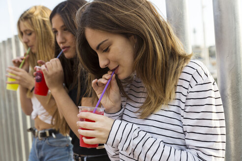 Young woman and her friends drinking beverages outdoors - KKAF00728
