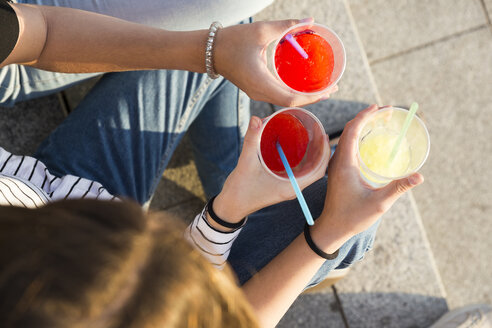 Three young women toasting with soft drinks, partial view - KKAF00731