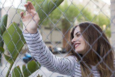 Portrait of smiling young woman behind wire fence - KKAF00734