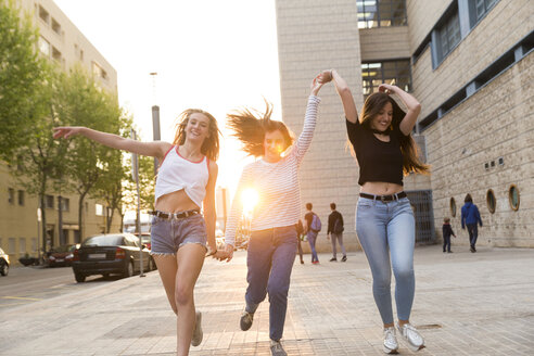 Three happy young women running hand in hand on sidewalk - KKAF00737