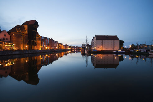 Poland, Gdansk, lighted row of houses with crane gate at Motlawa bank at dusk - ABOF00180