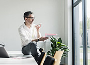 Businessman using cell phone in a conference room - UUF10497