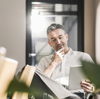 Smiling businessman sitting in an office using tablet - UUF10503