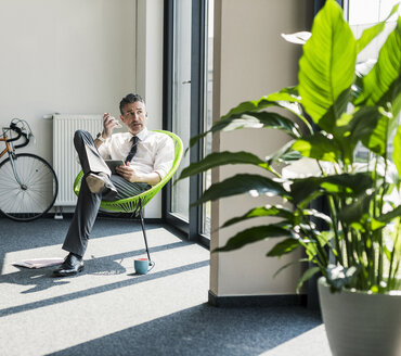 Businessman with tablet sitting in an armchair using smartphone and earphone for calling - UUF10512