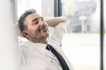 Portrait of smiling businessman with eyes closed listening music with earphones - UUF10524