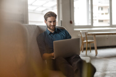Portrait of young freelancer sitting on couch in a loft using laptop - JOSF00729