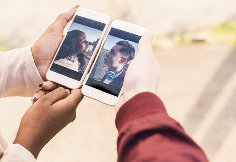 Hands holding smart phones with pictures of a young couple - UUF10532