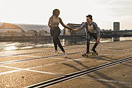 Young couple skateboarding at the riverside - UUF10538