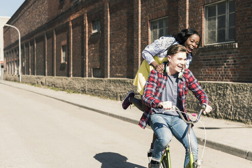 Young man riding bicycle with his girlfriend standing on rack - UUF10544