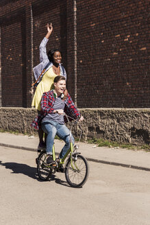Young man riding bicycle with his girlfriend standing on rack - UUF10547