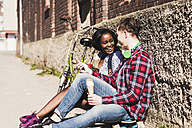 Young couple sitting on ground, eating icecream - UUF10550