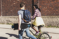 Young couple with bicycle and skateboard walking in the street - UUF10553