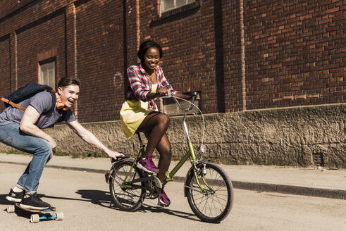 Young woman on bicycle pulling young man, standing on skateboard - UUF10556