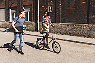 Young couple with bicycle and skateboard walking in the street - UUF10559