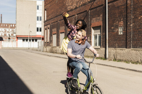 Young couple riding bicycle in the street, woman standing on rack, taking selfies - UUF10562