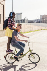 Young couple riding bicycle with girl standing on rack - UUF10565