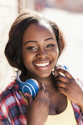 Portrait of a happy young woman with headphones around her neck - UUF10571