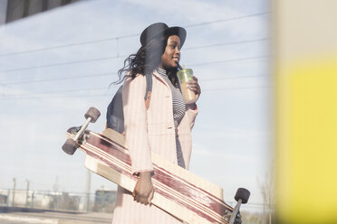 Young woman carrying skateboard, drining from disposable cup - UUF10574