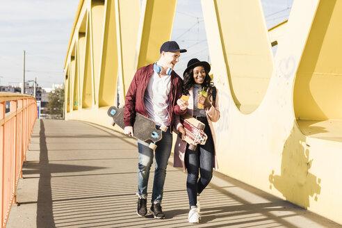 Young couple with skateboard walking on bridge - UUF10577