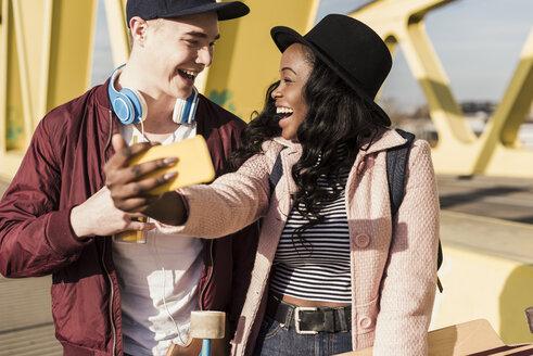 Young couple walking on bridge, using smartphone - UUF10580