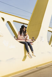 Young woman sitting on  bridge using smartphone - UUF10583