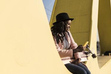 Young woman sitting on  bridge using smartphone - UUF10586