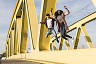 Happy couple jumping on bridge - UUF10589