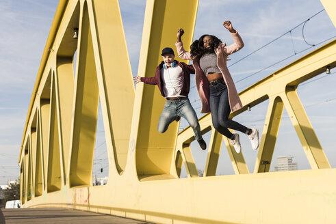Happy couple jumping on bridge - UUF10589