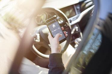 Man in car adjusting devices at home via smartphone - NAF00085