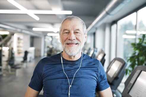 Portrait of fit senior man with earphones in gym - HAPF01649