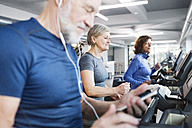 Group of fit seniors on treadmills working out in gym - HAPF01655