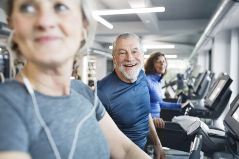 Group of fit seniors on treadmills working out in gym, man smiling - HAPF01658